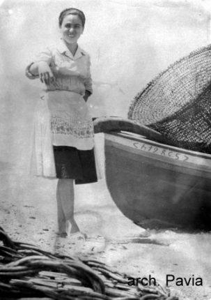Giovane donna di Marinella in posa vicino alla barca del marito  foto primi anni 60