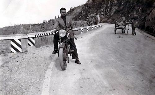 La strada Nazionale poche centinaia di metri prima del cimitero negli anni cinquanta  quando ancora si usavano i carri trascinati dai cavalli per trasportare le merci  sulla moto il sig. Rocco Lopresto